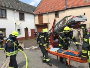 Das Bild zeigt Feuerwehrleute, die einen Verletzten mit einer Trage retten