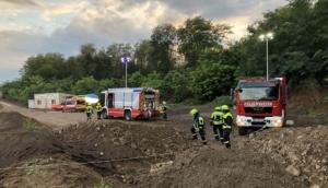 Foto zeigt die Feuerwehrfahrzeuge und Einsatzkräfte oberhalb der Abbaugrube.