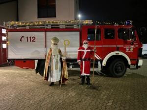 Das Foto zeigt •Nikolaus und Weihnachtsmann vor dem Tanklöschfahrzeug der Feuerwehr Plaidt.
