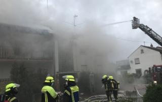 Foto zeigt die feuerwehr vor dem verrauchten Gebäude.