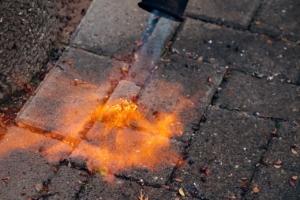 Foto zeigt das Abbrennen von Unkraut mit einem Gasbrenner